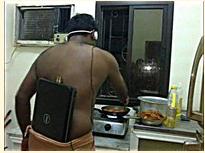 Изображение молодого человека у газовой плиты в наушниках и ноутбуком, заправленным в штаны