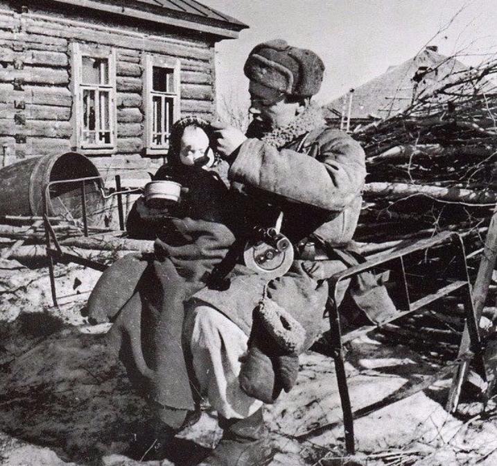 На фотографии Старший сержант Моисеев кормит двухлетнюю девочку, найденную им в одной из пустых изб в деревне Извеково, 1943 г.