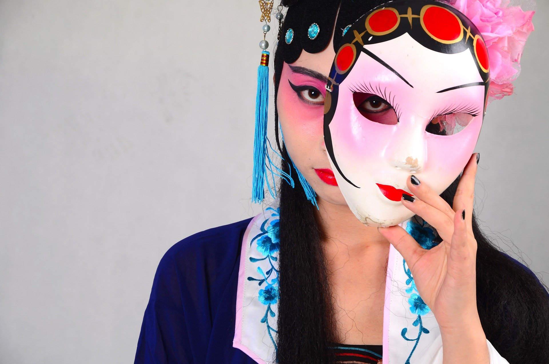 Фотокадр из пекинской оперы. Девушка держит маску.